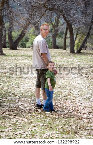 Father and son holding hands and walking in a wooded setting - stock photo