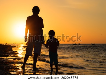 father and son holding hands at sunset sea - stock photo