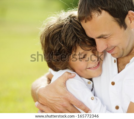 Father and son hugging and playing together in green nature - stock photo