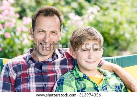 Father and son hugging sitting in the park over green nature - stock photo