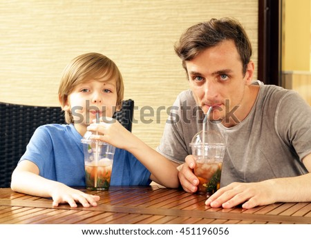 father and son in a cafe drinking ice tea - stock photo
