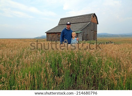 Father and son in a rural field with a rustic barn, Wyoming, USA. - stock photo