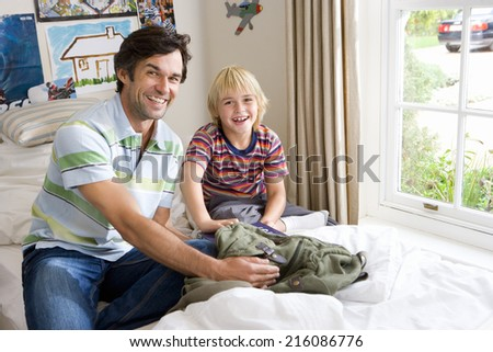 Father and son (6-8) in bedroom, smiling, portrait