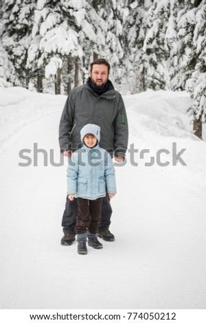 Father and son in forest snow