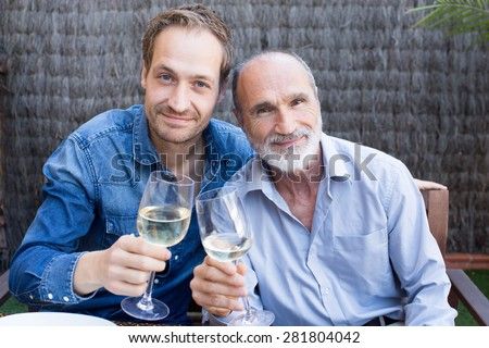 Father and son in garden drinking wine - stock photo