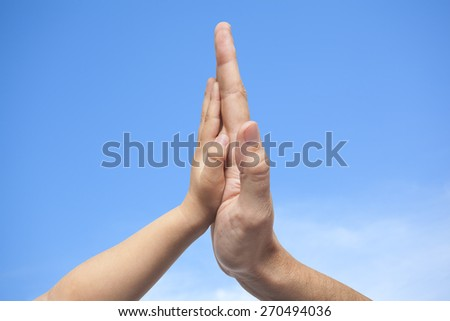 Father and son in high five gesture on a blue sky with some clouds background - stock photo