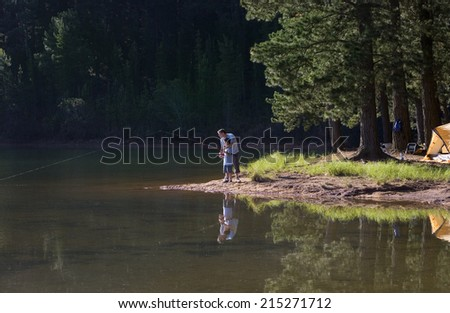 Father and son (8-10), in mid-distance, fishing in lake on camping trip, side view - stock photo