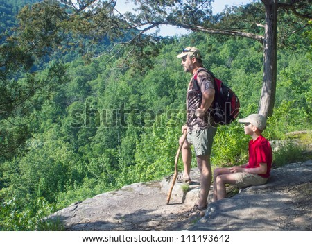 Father and son in the mountains admiring the scenery - stock photo