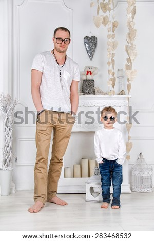 Father and son in white living room with a fireplace. Men's fashion - stock photo