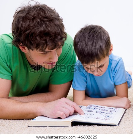 Father and son indoors reading book lying on floor