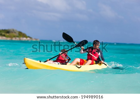 Father and son kayaking at tropical ocean - stock photo