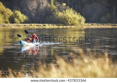 Father and son kayaking together on a lake, front view - stock photo