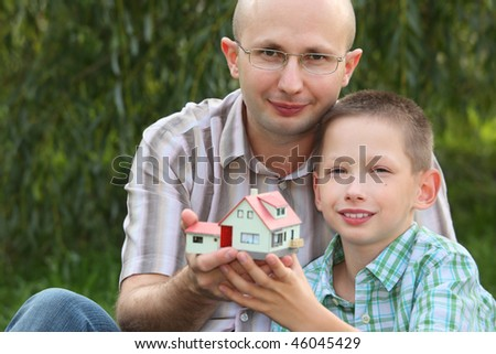 father and son keeping in their hands wendy house and looking at camera. focus on father's face. wendy house in out of focus. - stock photo