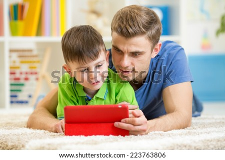 father and son kid playing with tablet computer at home - stock photo