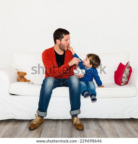 Father and son kidding together while eating pop corn on the couch - stock photo