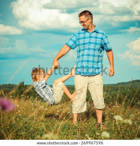 father and son laughing in an open space in a landscape - stock photo