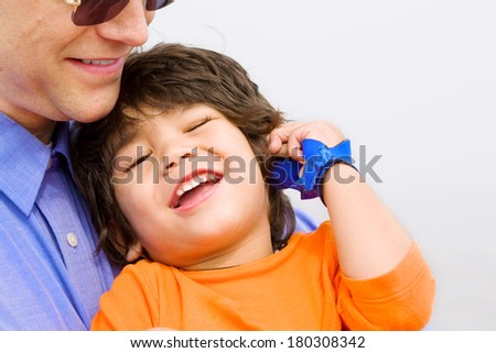 Father and son laughing together on beach. Child has cerebral palsy. - stock photo