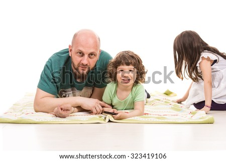 Father and son laying on blanket while girl playing in background - stock photo