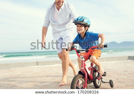 Father and son learning to ride a bicycle at the beach having fun together - stock photo