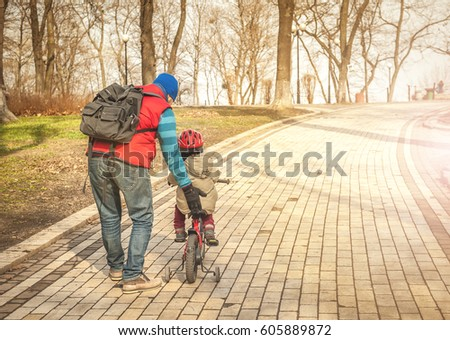 Father and son learning to ride a bicycle. happy toddler boy riding bike. Kids enjoying a bicycle ride. Active toddler. Sport concept.