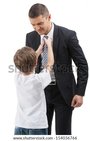 Father and son. Little boy adjusting his father necktie while isolated on white - stock photo
