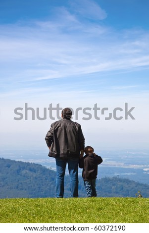Father and son looked into the distance from the cliff. - stock photo