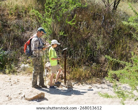 Father and son looking at a map and think and pointers on where to go. Saguaro National Park, Arizona, USA - stock photo