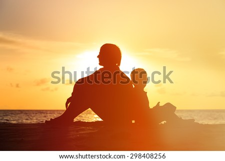 father and son looking at sunset on tropical beach - stock photo