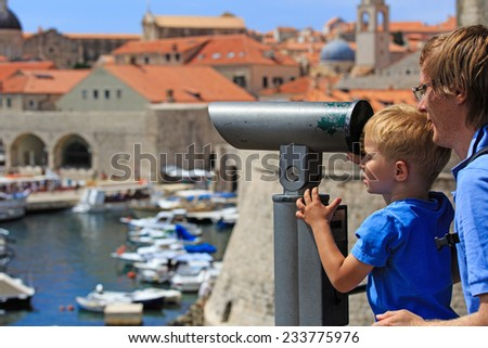father and son looking through binoculars at the city of Dubrovnik - stock photo