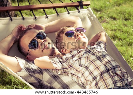Father and son lying on hammock in the garden at the day time. People having fun on the nature. Concept of friendly family and of summer vacation. - stock photo