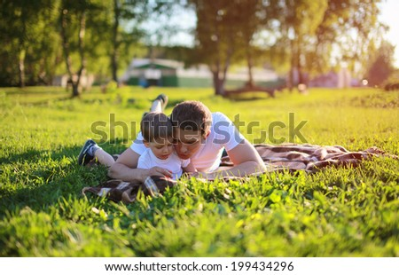 Father and son lying on the grass in weekend, family, vacation, lifestyle - concept. Sunlight on the sunset - stock photo
