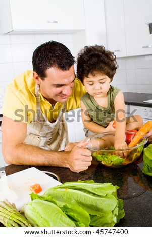father and son making green salad together in modern kitchen
