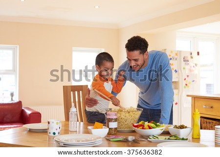 Father And Son Making Pasta Salad In Kitchen - stock photo