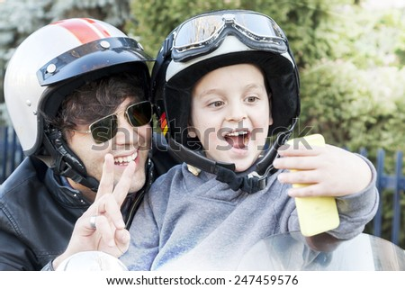 father and son motorcyclists take a selfie on the road - stock photo