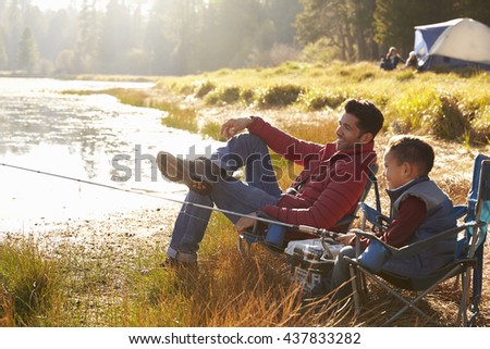Father and son on a camping trip fishing by a lake - stock photo