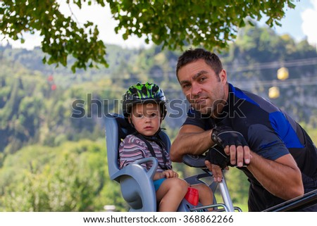 Father and son on a cycling trip using safety devices (helmets, child seat). Shallow DOF. - stock photo