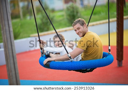 Father and son on a swing - stock photo