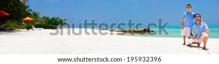 Father and son on a tropical beach vacation panorama - stock photo
