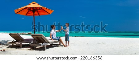 Father and son on a tropical beach vacation, panorama perfect for banners - stock photo