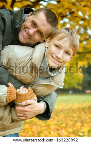 Father and son on a walk during the fall of the leaves in the park - stock photo