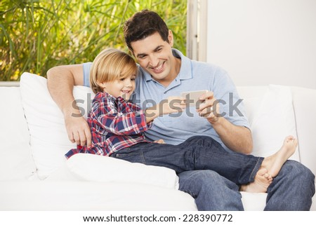 Father and son on couch taking selfies - stock photo