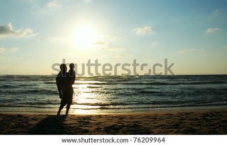 father and son on sunset - stock photo