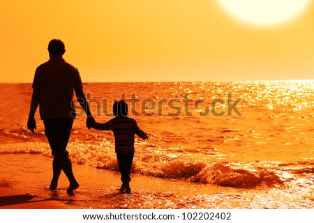 father and son on sunset at the beach - stock photo