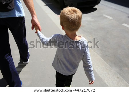 Father and son on the walk in the city - stock photo