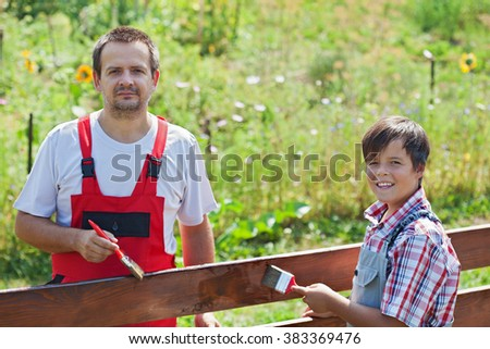 Father and son painting a wooden fence together on a sunny summer day- focus on boy