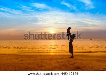 Father and son play on the Beach in sunrise silhouette shot - stock photo