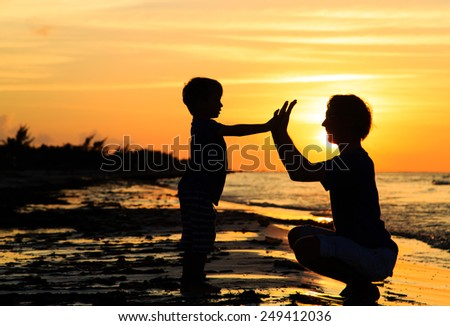 father and son playing at sunset sea - stock photo