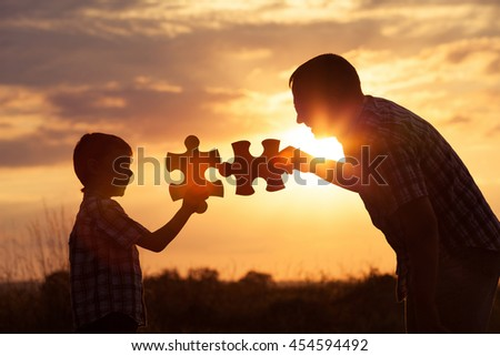 Father and son playing at the park at the sunset time. People having fun on the field. Concept of the kid is ready to go to school. - stock photo