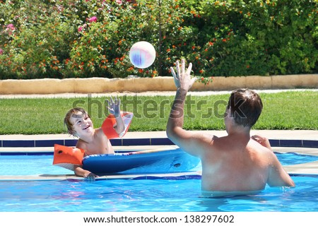 Father and son playing ball in a swimming pool - stock photo