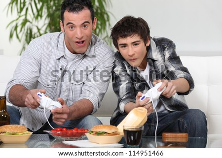 Father and son playing computer games and eating junk food - stock photo